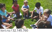 Group of elementary school children chatting on the green lawn. Стоковое видео, видеограф Яков Филимонов / Фотобанк Лори