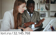 Купить «Young woman assistant and man manager working with laptop and papers in office», видеоролик № 32145768, снято 26 апреля 2019 г. (c) Яков Филимонов / Фотобанк Лори