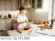 Купить «Young boy mixing melted chocolate in a bowl», фото № 32151080, снято 6 марта 2019 г. (c) Tryapitsyn Sergiy / Фотобанк Лори