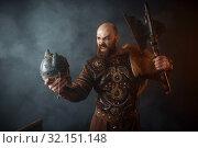 Купить «Angry viking holds enemy's skull in helmet and axe», фото № 32151148, снято 27 марта 2019 г. (c) Tryapitsyn Sergiy / Фотобанк Лори