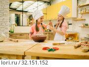 Купить «Little girls cooks in caps tastes vanilla powder», фото № 32151152, снято 30 марта 2019 г. (c) Tryapitsyn Sergiy / Фотобанк Лори