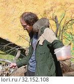 Купить «Moscow zoo. Zookeeper wiith Banded mongoose (Mungos mungo) on his shoulder», фото № 32152108, снято 29 августа 2019 г. (c) Валерия Попова / Фотобанк Лори