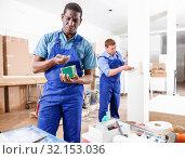 Купить «Two male builders working at indoors building site», фото № 32153036, снято 4 мая 2018 г. (c) Яков Филимонов / Фотобанк Лори