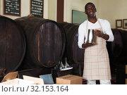Купить «Vintner proposing degustation of wine in store», фото № 32153164, снято 1 августа 2019 г. (c) Яков Филимонов / Фотобанк Лори