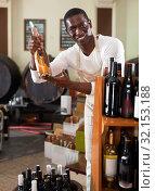 Купить «Smiling salesman in apron proposing wine in bottles in winery shop», фото № 32153188, снято 1 августа 2019 г. (c) Яков Филимонов / Фотобанк Лори