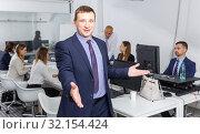 Купить «Successful businessman standing in office with open hand», фото № 32154424, снято 21 апреля 2018 г. (c) Яков Филимонов / Фотобанк Лори