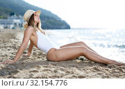 Купить «Female in swimsuit taking sunbath at sand at sea shore on sunny day», фото № 32154776, снято 10 июля 2018 г. (c) Яков Филимонов / Фотобанк Лори