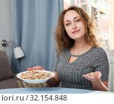 Купить «Woman eating pistachios at home», фото № 32154848, снято 17 октября 2019 г. (c) Яков Филимонов / Фотобанк Лори