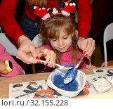 Девочка посыпает елочную игрушку блестками. Детский мастер-класс в мастерской. Стоковое фото, фотограф Ирина Борсученко / Фотобанк Лори
