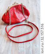 Little red leather women's handbag on wooden table. Стоковое фото, фотограф Zoonar.com/Valery Voennyy / easy Fotostock / Фотобанк Лори