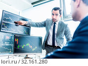 Купить «Businessmen trading stocks online. Stock brokers looking at graphs, indexes and numbers on multiple computer screens. Colleagues in discussion in traders office. Business success concept.», фото № 32161280, снято 9 июля 2020 г. (c) easy Fotostock / Фотобанк Лори