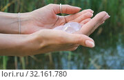 Female hand holding a rose quartz and amethyst crystal yoni eggs on river background. Women's health, unity with nature concepts. Стоковое видео, видеограф Ольга Балынская / Фотобанк Лори