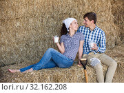 Купить «man and woman in hay with milk», фото № 32162208, снято 17 сентября 2019 г. (c) Яков Филимонов / Фотобанк Лори