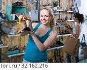 Купить «girl holding a picked pair of shoes in the boutique», фото № 32162216, снято 21 сентября 2019 г. (c) Яков Филимонов / Фотобанк Лори