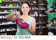Купить «Charming woman customer is showing modern heeled sandals», фото № 32162464, снято 10 мая 2017 г. (c) Яков Филимонов / Фотобанк Лори
