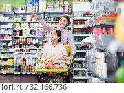 Купить «Woman with girl looking for food in supermarket», фото № 32166736, снято 5 января 2017 г. (c) Яков Филимонов / Фотобанк Лори