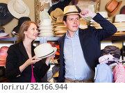 Купить «Girl and male try on modern hats at the boutique», фото № 32166944, снято 2 мая 2017 г. (c) Яков Филимонов / Фотобанк Лори