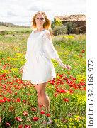 Купить «Female in white dress walking through a poppy field of wild flowers», фото № 32166972, снято 8 апреля 2019 г. (c) Яков Филимонов / Фотобанк Лори