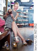Купить «Glad young girl shopaholic holding desired shoe», фото № 32167052, снято 20 сентября 2019 г. (c) Яков Филимонов / Фотобанк Лори