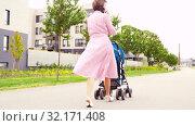 Купить «mother with stroller calling on smartphone in city», видеоролик № 32171408, снято 1 сентября 2019 г. (c) Syda Productions / Фотобанк Лори