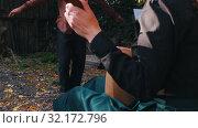 A woman playing the balalaika and a man dancing folklore dancing near the country house - bright sunlight. Стоковое видео, видеограф Константин Шишкин / Фотобанк Лори