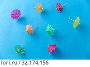 Купить «cocktail umbrellas on blue background», фото № 32174156, снято 20 ноября 2018 г. (c) Syda Productions / Фотобанк Лори