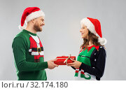 Купить «happy couple in christmas sweaters with gift box», фото № 32174180, снято 9 декабря 2018 г. (c) Syda Productions / Фотобанк Лори