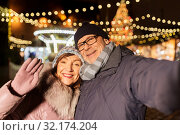 Купить «senior couple taking selfie at christmas market», фото № 32174204, снято 27 декабря 2018 г. (c) Syda Productions / Фотобанк Лори