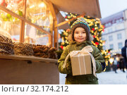 Купить «happy boy with gift box at christmas market», фото № 32174212, снято 4 января 2019 г. (c) Syda Productions / Фотобанк Лори