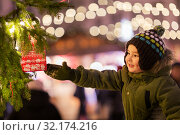 Купить «boy reaching to gift bag hanging on christmas tree», фото № 32174216, снято 4 января 2019 г. (c) Syda Productions / Фотобанк Лори