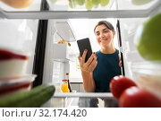 Купить «woman with smartphone makes list of food in fridge», фото № 32174420, снято 15 августа 2019 г. (c) Syda Productions / Фотобанк Лори