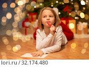 girl writing christmas wish list at home. Стоковое фото, фотограф Syda Productions / Фотобанк Лори