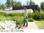 Купить «young woman watering flowers at garden», фото № 32174496, снято 12 июля 2019 г. (c) Syda Productions / Фотобанк Лори