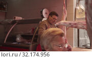 Купить «A butchershop. Meat carcasses hunged on hooks. Butcher cuts lamb along spine», видеоролик № 32174956, снято 18 мая 2019 г. (c) Ирина Мойсеева / Фотобанк Лори