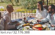 Купить «Friends having lunch on the open-air terrace», видеоролик № 32176388, снято 26 апреля 2019 г. (c) Яков Филимонов / Фотобанк Лори