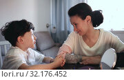 Купить «Cheerful woman telling funny story to her teenage son at home table», видеоролик № 32176452, снято 26 апреля 2019 г. (c) Яков Филимонов / Фотобанк Лори
