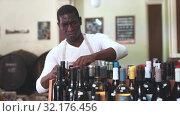 Купить «Confident male vintner choosing wine bottle on shelf rack and proffering to buy in modern wine shop», видеоролик № 32176456, снято 16 сентября 2019 г. (c) Яков Филимонов / Фотобанк Лори