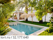 Купить «Inner garden with private swimming pool straw parasol beautiful luxury wealthy residential summer villa, sunny day, no people. Spain», фото № 32177640, снято 2 июля 2019 г. (c) Alexander Tihonovs / Фотобанк Лори