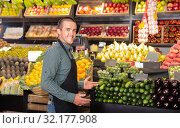 Male shop assistant standing of counter of vegetable shop. Стоковое фото, фотограф Яков Филимонов / Фотобанк Лори