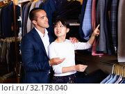 Купить «Portrait of young family couple looking for new suit jacket in men clothes shop», фото № 32178040, снято 7 апреля 2020 г. (c) Яков Филимонов / Фотобанк Лори