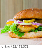 Купить «Delicious tasty burger with chicken cutlet, vegetables and cheese», фото № 32178372, снято 22 октября 2019 г. (c) Яков Филимонов / Фотобанк Лори