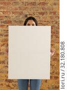 Купить «Blank canvas held in front of brick wall», фото № 32180808, снято 23 июля 2019 г. (c) Wavebreak Media / Фотобанк Лори