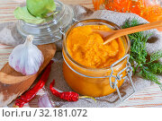 Homemade canning of the autumn harvest, vegetable vegetarian diet wholesome food, spicy mashed caviar from orange pumpkin, carrots and zucchini with garlic, red pepper and fresh dill in a glass jar. Стоковое фото, фотограф Светлана Евграфова / Фотобанк Лори