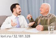 Купить «Elderly man and agent rent apartments», фото № 32181328, снято 20 ноября 2019 г. (c) Яков Филимонов / Фотобанк Лори