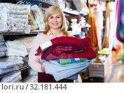 Купить «Positive mature woman choosing cotton bedcover in the textile shop», фото № 32181444, снято 17 января 2018 г. (c) Яков Филимонов / Фотобанк Лори