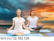 Купить «women meditating in yoga lotus pose outdoors», фото № 32182128, снято 7 августа 2016 г. (c) Syda Productions / Фотобанк Лори