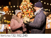 happy senior couple with gift at christmas market. Стоковое фото, фотограф Syda Productions / Фотобанк Лори