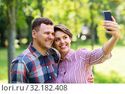 Купить «happy couple in park taking selfie by smartphone», фото № 32182408, снято 18 августа 2019 г. (c) Syda Productions / Фотобанк Лори