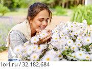 Купить «happy woman smelling chamomile flowers in garden», фото № 32182684, снято 12 июля 2019 г. (c) Syda Productions / Фотобанк Лори