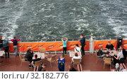 Купить «Пассажиры на корме круизного парома. Столы, стулья, кушетки на палубе. Круиз на лайнере Viking Line в Балтийском море», видеоролик № 32182776, снято 17 июня 2019 г. (c) Кекяляйнен Андрей / Фотобанк Лори